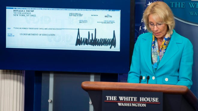 Education Secretary Betsy DeVos is pictured speaking about President Trump's donation to the Department of Education.