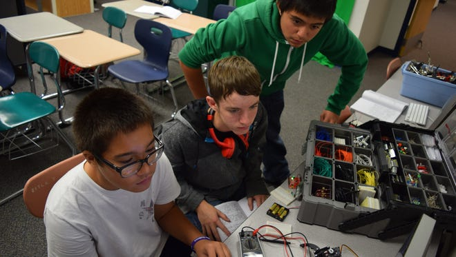 Joseph Hoersten, Eric Wingo and Alan Sapp, 8th graders at Holloman Middle School, work on their prototype for the Samsung Solve for Tomorrow contest. Holloman's team designed and created a device that can sense an amount of standing water and send out an alert.