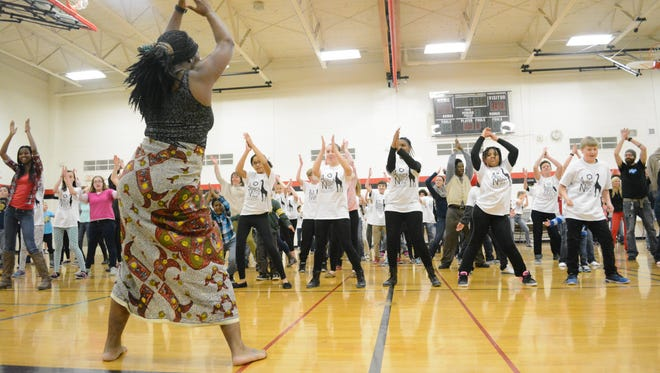 Althea René Miller leads seventh grade students and families from Roosevelt Middle School and Kaleidoscope Academy Thursday in an African dance as part of Africa Night.