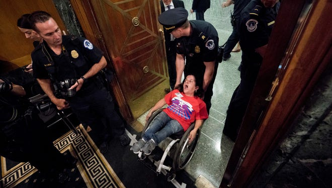 A woman in a wheelchair is removed after disrupting a Senate Finance Committee hearing to consider the Graham-Cassidy healthcare proposal, on Capitol Hill, Sept. 25, 2017, in Washington.