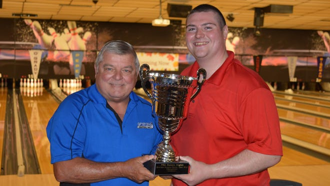 Terry Brenneman, proprietor of Colony Park Lanes North, left, presents the PBA Bowlers Supply/Storm Open trophy to Darren Andretta of Mantagh, New York.  Andretta also won $2,500.