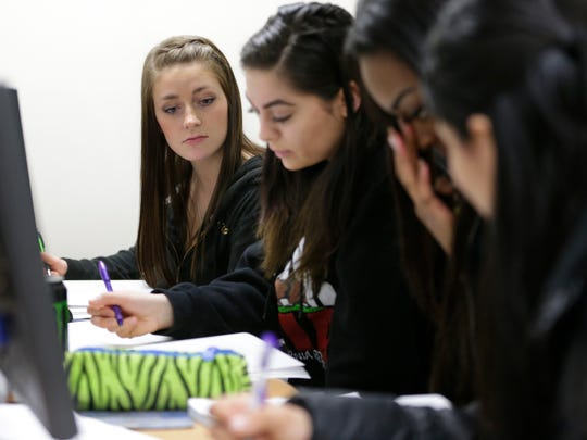 Northeast Wisconsin Technical College student Melissa Cumber, left, works on a reading assignment with, from right, Paula Barajas, Shakira Butler and Julia Robles.