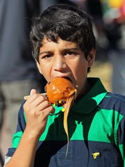 Ankith Tenneti age 10 of Wauwatosa, took a bite out of a caramel apple he bought at Harvest Fair. MICHAEL SEARS/MSEARS@JOURNALSENTINEL.COM