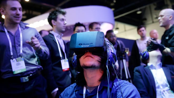 FILE - In this Jan. 7, 2014 file photo, show attendees play a video game wearing  Oculus Rift virtual reality headsets at the Intel booth at the International Consumer Electronics Show(CES), in Las Vegas.