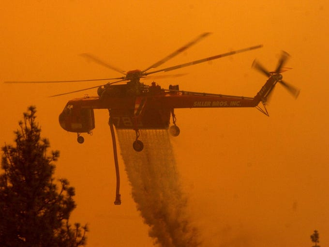 ANGORA FIRE: A helicopter releases its load of water