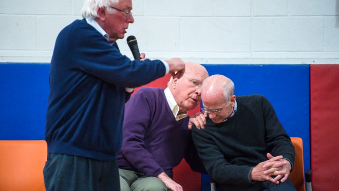 U.S. Senator Patrick Leahy, center, and U.S. Rep. Peter Welch confer as U.S. Senator Bernie Sanders, left, speaks during a town hall meeting held by Vermont's congressional delegation at Hazen Union High School in Hardwick on Saturday, March 25, 2017.