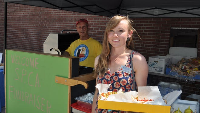 SPCA of Tompkins County worker Sarah Post picks up a box of dogs at the fundraiser