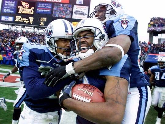 The Titans' Kevin Dyson, center, holds onto the ball as he celebrates with teammates Yancey Thigpen, left, and Samari Rolle after returning a kickoff for a touchdown with 3 seconds left in their AFC wild-card game against the Bills for a 22-16 victory Jan. 8, 2000.