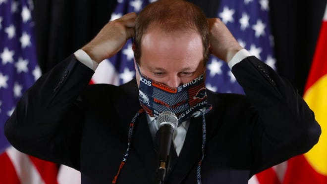 [AP FILE PHOTO] Gov. Jared Polis dons a face mask at a news conference in May.