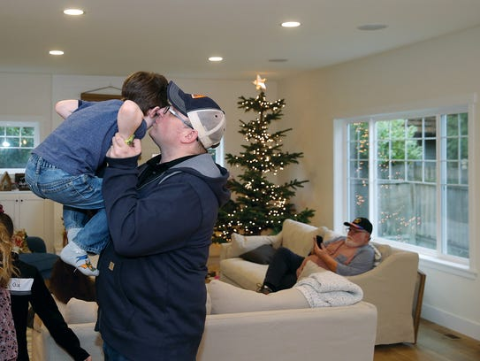 Steven Hays lifts and kisses his son Grayson, 7, inside their new Central Kitsap Home on Thursday.