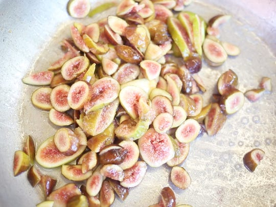 Katie Tillman sautŽs figs before adding balsamic vinegar to create a reduction on July 19 at the Anderson County Farmers Market.