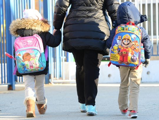 Parents arrive to school with their children after