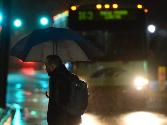 A man uses an umbrella to shield him from the rain as he waits for an NJ Transit bus on Valley Blvd in Wood-Ridge on Friday morning March 2, 2018.