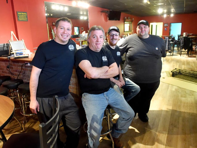 Owner Mike McMackin (center) sits as kitchen manager