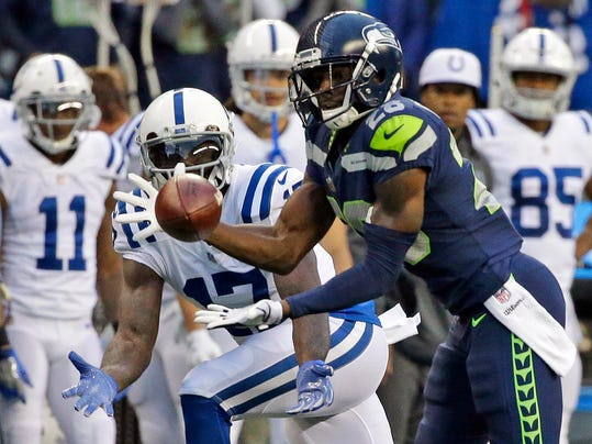 FILE - In this Oct. 1, 2017, file photo,  Seattle Seahawks cornerback Justin Coleman, right, intercepts a pass intended for Indianapolis Colts wide receiver Kamar Aiken, center, in the first half of an NFL football game in Seattle. Coleman returned the interception for a touchdown. This year it's the likes of J.D. McKissic, Justin Coleman and Marcus Smith have gone from discarded to major contributors for the Seahawks now and moving forward after their bye week.   (AP Photo/Elaine Thompson, File)