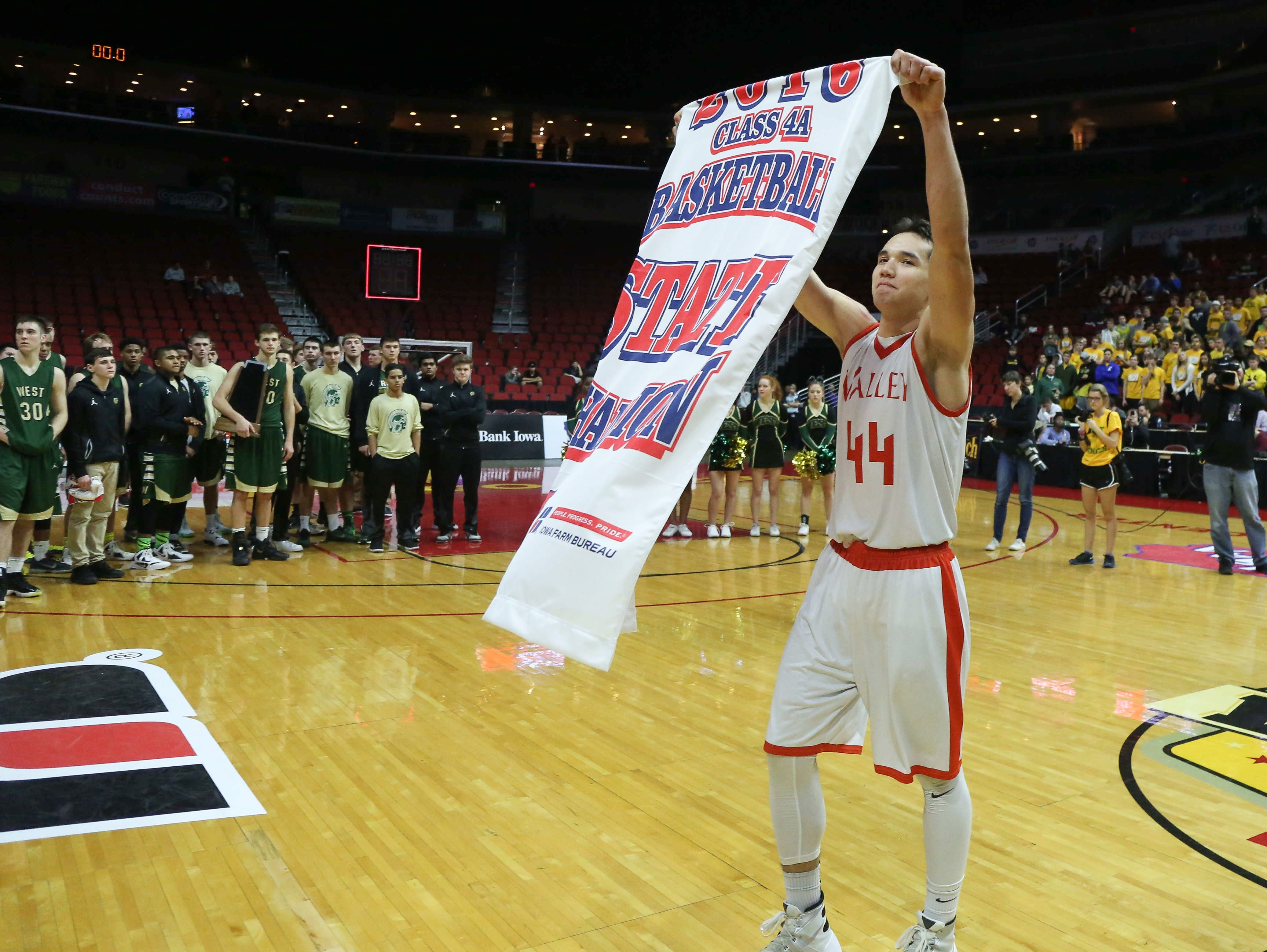 Valley junior Quinton Curry holds the Class 4A state championship banner after the Tigers beat Iowa City West on Saturday, March 12, 2016, at Wells Fargo Arena in Des Moines.