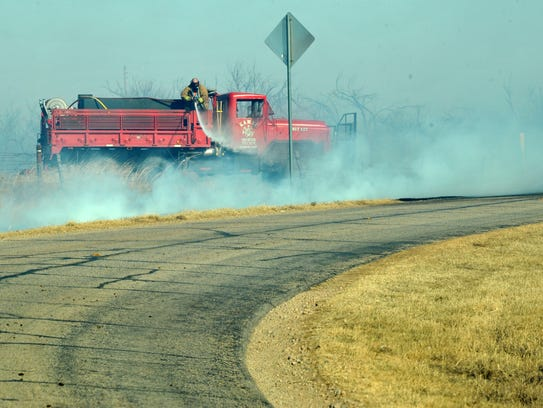Firefighters from the Kamay Volunteer Fire Department work to contain a grass fire Monday afternoon that burned an estimated 500 to 1,000 acres.