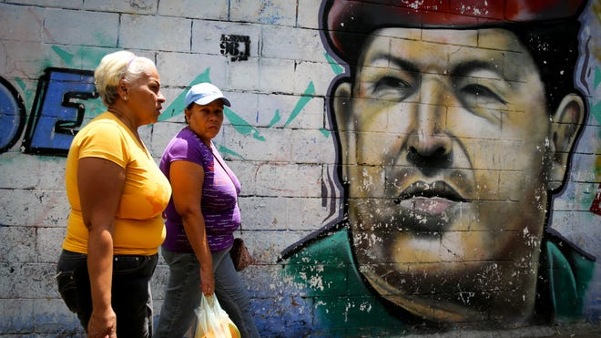 Two shoppers in the pro-government Caracas district of 23 de enero pass a mural of former president Hugo Chávez. Many here supported Chávez but are lukewarm toward his successor Nicolás Maduro.