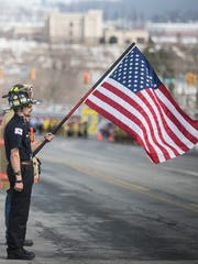 Jefferson Fire Police Lt. Brandon Soltes looks on, as Wellsville EMT Tyler Bell, front, holds an american flag, while Lt. Dennis H. DeVoe's Funeral Procession begins down East Forrest Ave. Saturday, March 18, 2017, in Shrewsbury. Amanda J. Cain photo