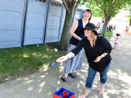 Prairie City native Kilah McDonald (right) and Brandi Helms of Ankeny play a washer toss game on Saturday, August 8, 2015, during Ankeny Unplugged sponsored by Ankeny Jaycees and held at Wagner Park.