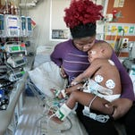 Quintrissa Everhart  holds her daughter, Lyric Everhart, a 20-month-old heart patient at Le Bonheur Children's Hospital, while Quintrell Everhart, the baby's uncle, tries to cheer her up. On Saturday the hospital's Heart Institute performed a heart transplant on Lyric, who suffered acute heart failure.