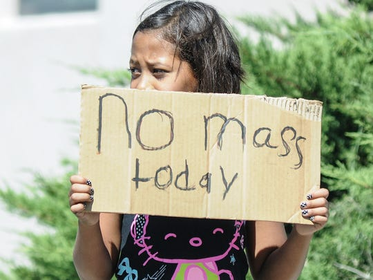 Aaliyah Dominguez, 11, stands on North Alameda Boulevard advising parishioners of Holy Cross Catholic Church that Mass is canceled on Aug. 2, 2015.