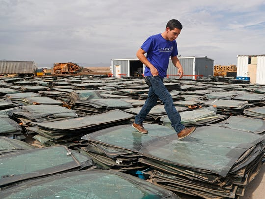 Blake King walks across some of the thousands of windshields