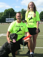 Harper Creek football coach Mike Seedorff, along with his daughter Madison, with their dog Hank, who is one of the top dock jumping dogs in the country.