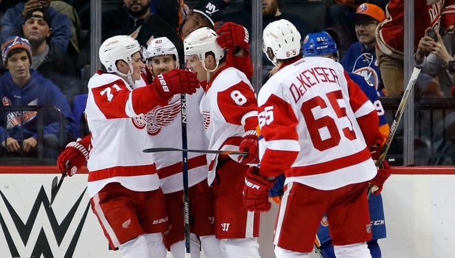 Dylan Larkin (71) and Henrik Zetterberg (40) celebrate with Justin Abdelkader (8) after Abdelkader scored in the second period.