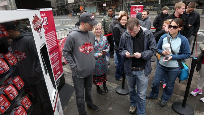"""Kevin Losekamp of Amelia uses his phone to tweet at the All-Star Game """"Twitter vending machine"""" for prizes on Fountain Square during a recent promotion for the All-Star Game Fanfest that will run from July 10-14."""