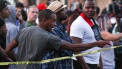 A man points at police as he and others visit the scene