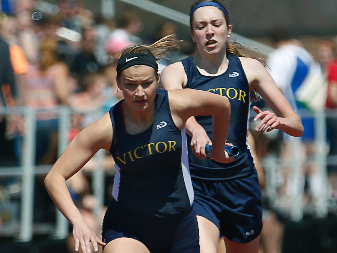 Victor's Carly Oddi takes the baton from Erika Tillotson for the sprint medley relay during the track and field meet at Rush-Henrietta High School on April 18, 2015.
