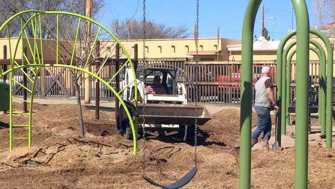 Employees from Exerplay Inc., work on getting the ground situated before installing the crum rubber at Penny Park. The work should be completed by this weekend so that the Park can open Monday.