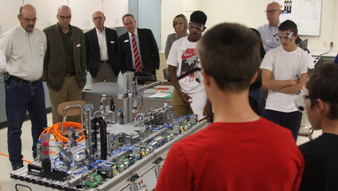 From left to right in background: Steve Smith of Vulcan Industries; Pat Finney, HSC plant manager; Wayne Wilkinson; Jack Turner; Katie Gambill; and Lawson Mabry observe students at Kenwood High School using the mechatronics equipment at the school.