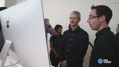 Apple CEO Tim Cook looks at the new iMac