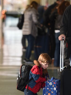 Neil Coleman prepares his baggage alongside his family for air travel at McGhee Tyson Airport Wednesday, Nov. 23, 2016. The day before the Thanksgiving holiday is the busiest travel day of the year.