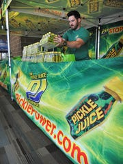 Robert Poyser of Pickle Juice adds to the company's display at the Hotter 'N Hell Hundred Consumer Show Thursday afternoon. The product helps stop muscle cramps and provides large amounts of electrolytes for hydration.