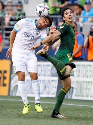 Seattle Sounders FC midfielder Cristian Roldan (7) heads a ball away from Portland Timbers defender Zarek Valentin (16) during the first half at CenturyLink Field.
