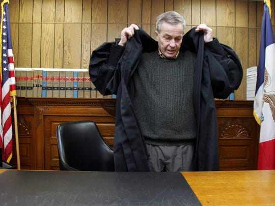 Iowa Supreme Court Justice Jerry Larson pulls on his robe behind the 1890s-era hand-carved judge's bench in the Shelby County Courthouse Friday, April 18, 2008. Justice Larson began his legal career working in front of that bench as the Shelby County attorney in the 1960s, then served as a judge behind it. He was appointed to the Iowa Supreme Court in 1978, and retired in May 2008 as the longest-serving member of bench in Iowa Supreme Court history.