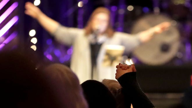 Lori Glendenning sings as those in attendance join hands during a gathering at Christ the Rock Community Church Wednesday following the death of founder and senior pastor Bill Lenz.