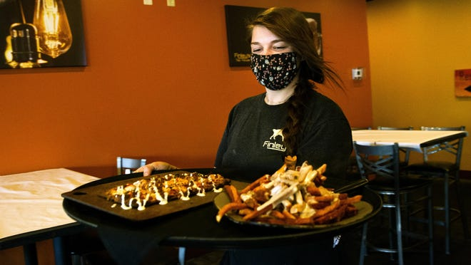 Dakota Barker wears a face mask as she carries a customer's order to their table at Finley's Tap House in Springfield Monday, July 13, 2020.