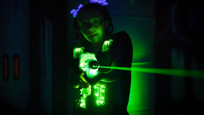 A little girl playing laser tag.