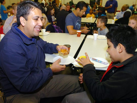 Ever Quezada, 10, and his dad, Juan, munch on doughnuts together.