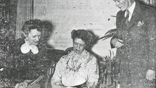 """The original caption from the Asheville Times for this photo read, """"Mrs. Franklin D. Roosevelt, center, is shown above as she glanced over the program outlined for sessions of the Council of Southern Mountain Workers, the opening meetings of which she attended today. Later today she was to visit the army redistribution center here. Tomorrow she will speak at Warren Wilson junior college at Swannanoa. With her are shown Mr. and Mrs. Arthur Bannerman. Mr. Bannerman, Warren Wilson president, is directing the social worker's two-day parlay."""""""