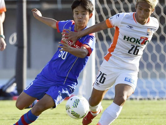 In this Nov. 5, 2016 photo, FC Tokyo youth player Takefusa Kubo, left, vies for the ball during a J3 soccer match in Tokyo. FIFA Under-20 World Cup kicks off in South Korea on Saturday, May 20, 2017. Kubo spent four years playing for Barcelona's youth team before signing for FC Tokyo in 2016. Still just 15, the midfielder made his first team debut for the club in a cup match earlier in May and is already a star in Japan. (Shigeyuki Inakuma/Kyodo News via AP)