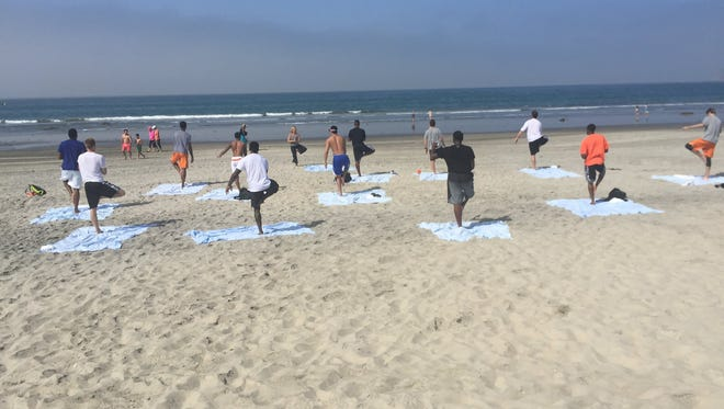 Eric Bledsoe leads Suns teammates in a yoga session on a beach in San Diego earlier this week.