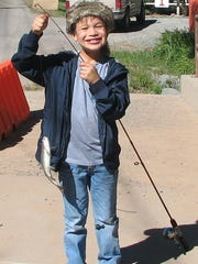 A proud young fisherman shows off his catch.