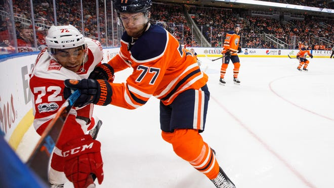 Red Wings forward Andreas Athanasiou is checked by the Oilers' Oscar Klefbom during the third period of the Wings' win Sunday in Edmonton, Alberta.