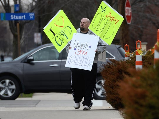 Green Bay resident Rick Lentz, whose brother is a police office, but also says he has also been arrested by Green Bay police multiple times, walks on Adams Street in front of the Green Bay Police Department wearing signs supporting them.