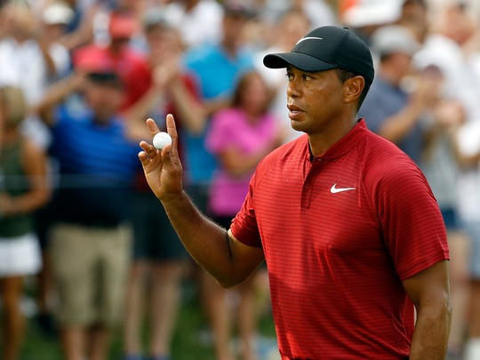 Tiger Woods waves to the crowd after sinking a birdie putt on the 15th green during the final round of the PGA Championship golf tournament at Bellerive Country Club, Sunday, Aug. 12, 2018, in St. Louis. (AP Photo/Charlie Riedel)